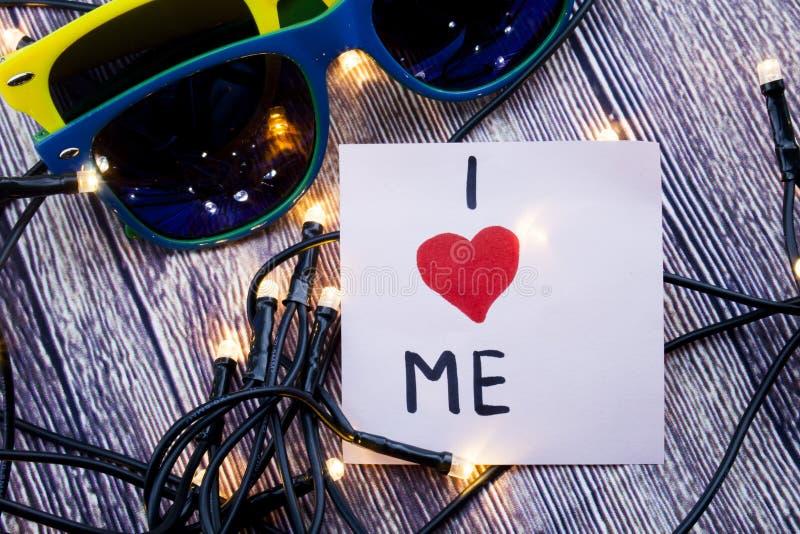 Με αγαπώ στην κολλώδη σημείωση με τα γυαλιά ηλίου σε ένα ξύλινο υπόβαθρο με την έννοια φω'των για την αγάπη για σας μόνη αγάπη στοκ εικόνα