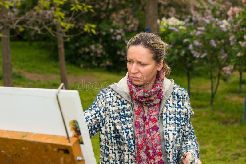 Μελαγχολικός θηλυκός καλλιτέχνης κατά τη διάρκεια μιας κατηγορίας τέχνης σε ένα πάρκο στοκ φωτογραφία με δικαίωμα ελεύθερης χρήσης
