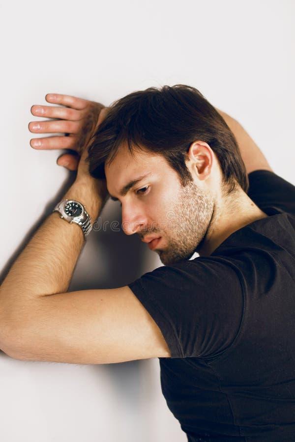 Μελαγχολικός και λυπημένος τύπος σε μια μαύρη μπλούζα και ρολόι σε ετοιμότητα στοκ φωτογραφία