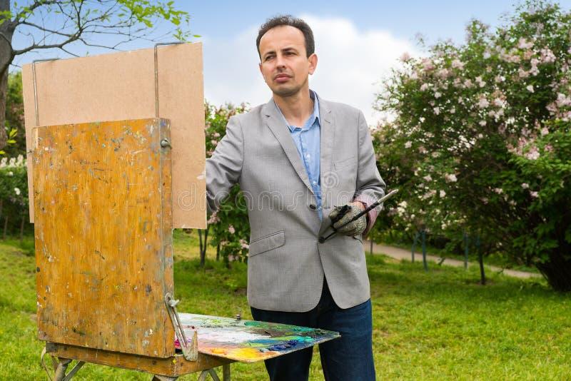 Μελαγχολικός όμορφος μέσης ηλικίας αρσενικός καλλιτέχνης που χρωματίζει ένα masterpi στοκ φωτογραφία με δικαίωμα ελεύθερης χρήσης