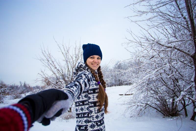 Με ακολουθήστε Ελκυστική νέα γυναίκα στο χέρι εκμετάλλευσης καπέλων του φίλου και του περπατήματός της στοκ φωτογραφία με δικαίωμα ελεύθερης χρήσης