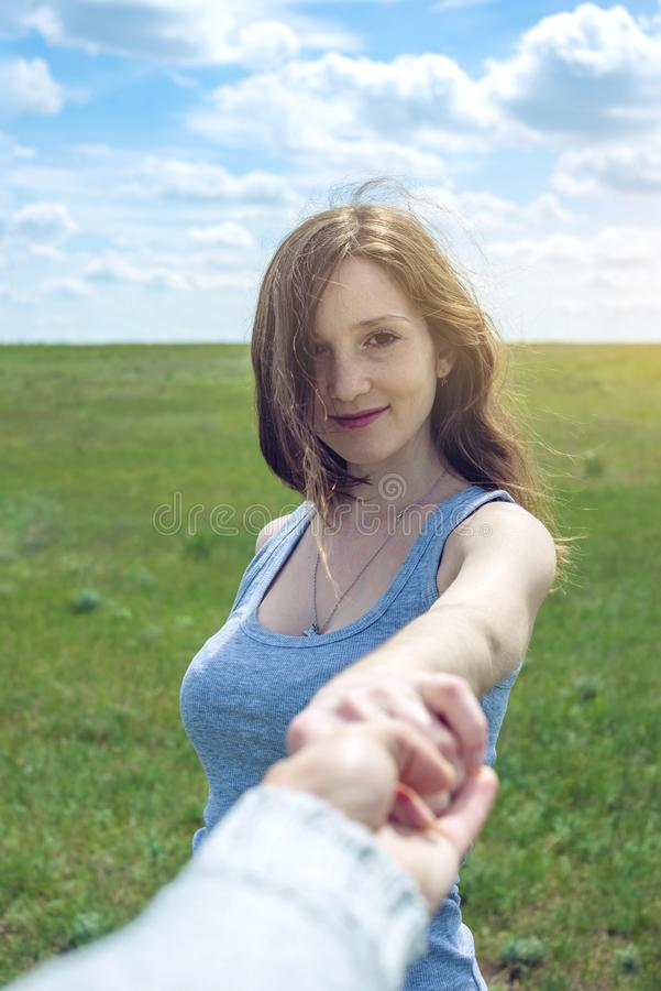 Με ακολουθήστε, ελκυστικό κορίτσι brunette που κρατά το χέρι των μολύβδων σε έναν καθαρό πράσινο τομέα, στέπα με τα σύννεφα στοκ εικόνες