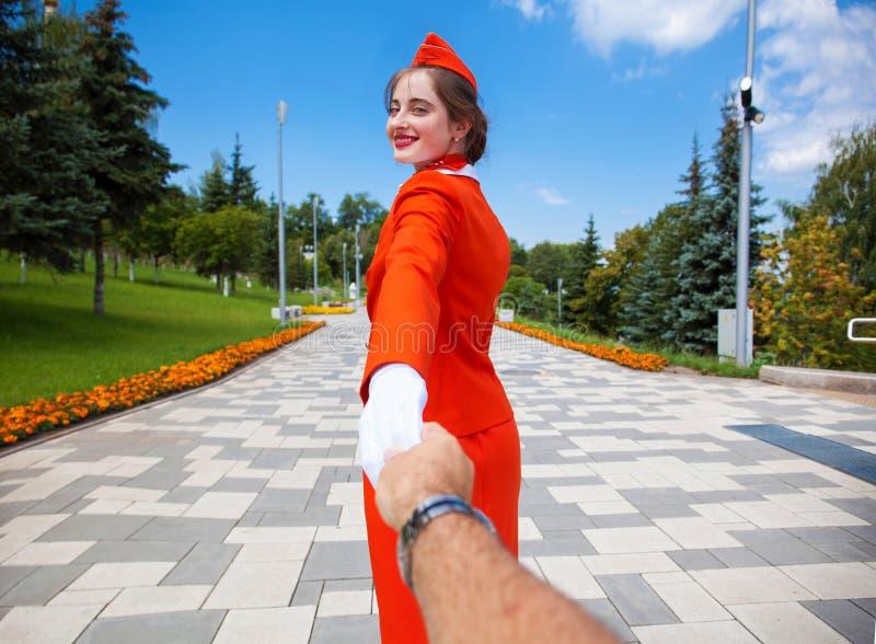 Με ακολουθήστε, νέα αεροσυνοδός που ντύνεται επίσημο κόκκινο σε ομοιόμορφο των αερογραμμών, θερινό πάρκο υπαίθρια στοκ φωτογραφία με δικαίωμα ελεύθερης χρήσης
