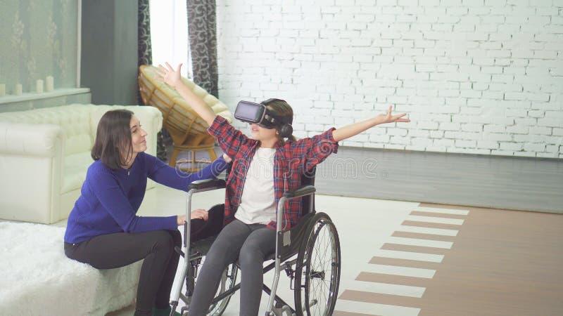 Με ειδικές ανάγκες έφηβος σε μια αναπηρική καρέκλα και το mom της που χρησιμοποιεί στο σπίτι vr την τεχνολογία στοκ φωτογραφία με δικαίωμα ελεύθερης χρήσης