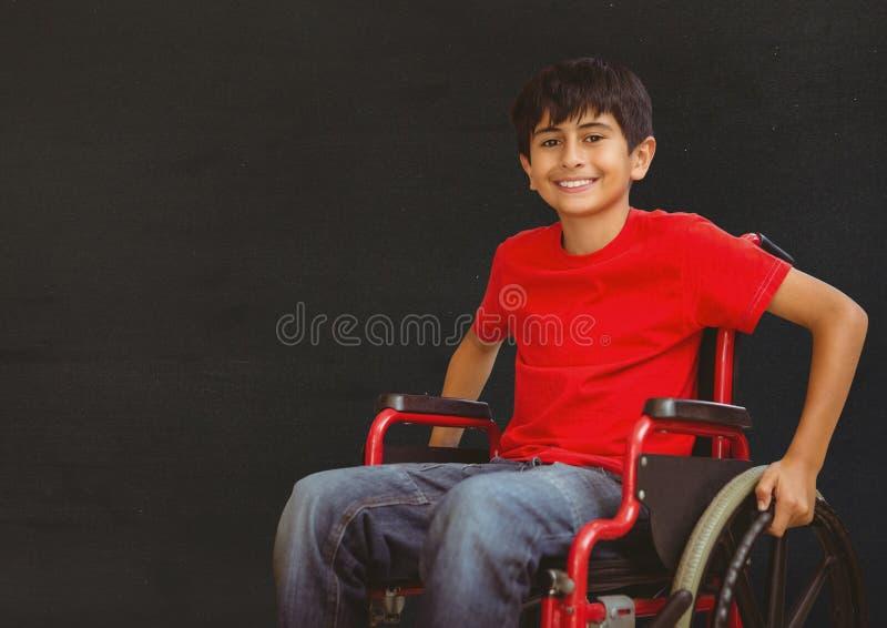 Με ειδικές ανάγκες αγόρι στην αναπηρική καρέκλα μπροστά από τον πίνακα στοκ εικόνα