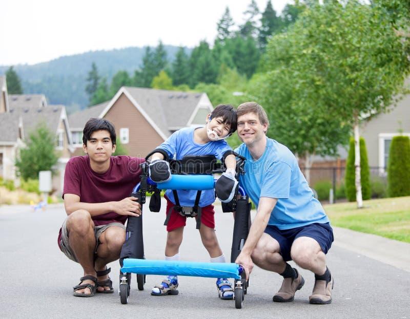 Με ειδικές ανάγκες αγόρι στον περιπατητή, με τον πατέρα και τον αδελφό στοκ εικόνες