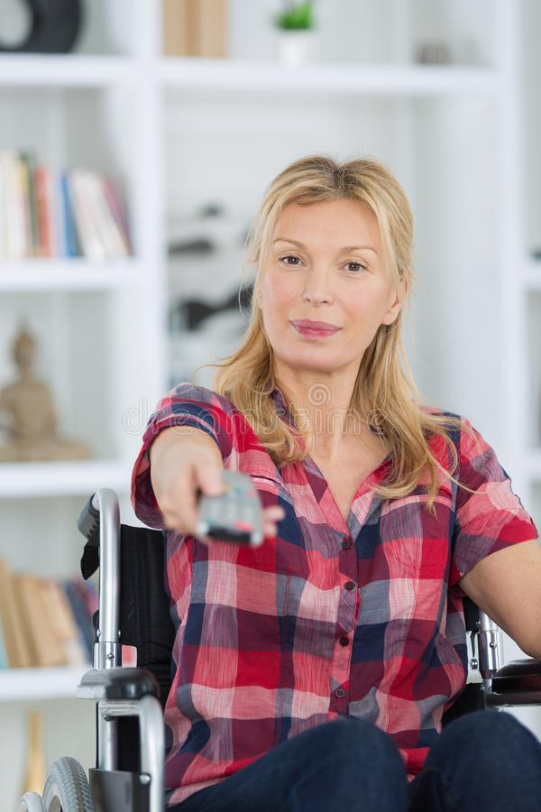 Με ειδικές ανάγκες ανώτερη γυναίκα που προσέχει τη TV στο καθιστικό στοκ φωτογραφίες