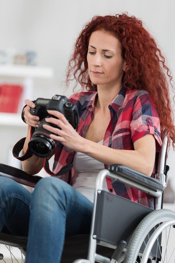 Με ειδικές ανάγκες γυναίκα που παίρνει τις εικόνες με τη κάμερα dslr στοκ εικόνες
