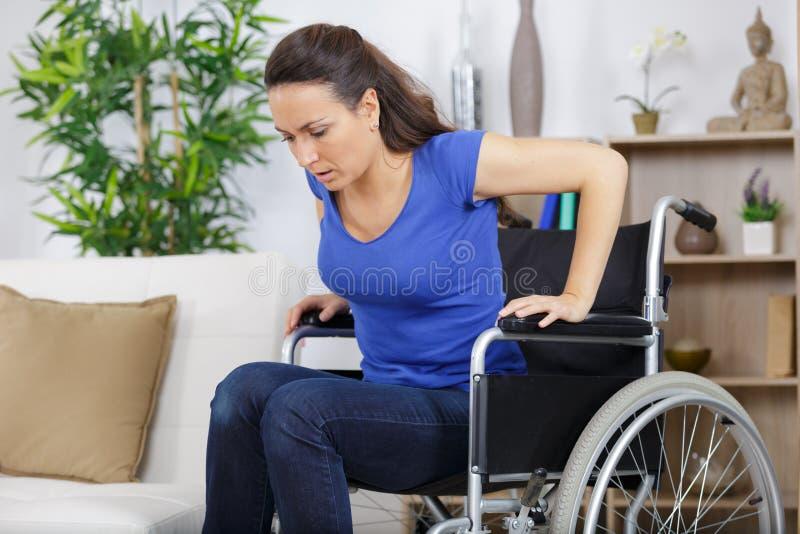 Με ειδικές ανάγκες γυναίκα στην αναπηρική καρέκλα που προσπαθεί να καθίσει στον καναπέ στοκ εικόνα