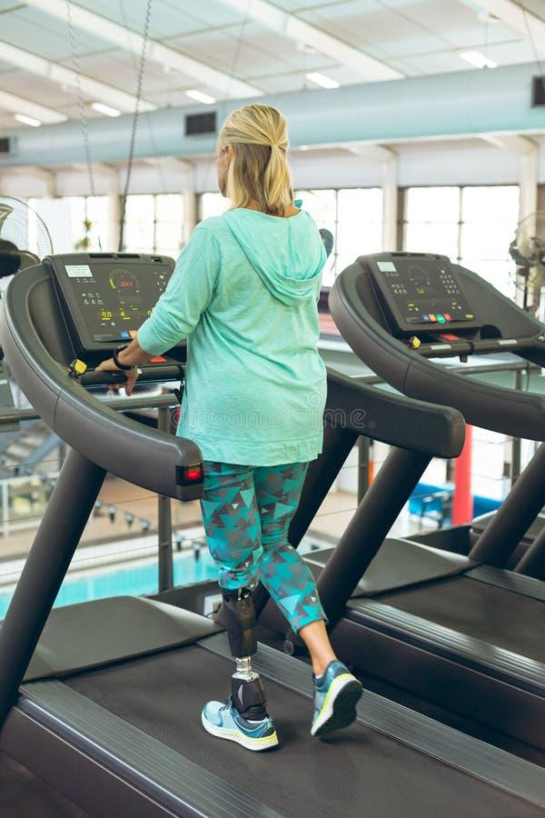 Με ειδικές ανάγκες ενεργός ανώτερη γυναίκα που ασκεί treadmill στο στούντιο ικανότητας στοκ φωτογραφίες