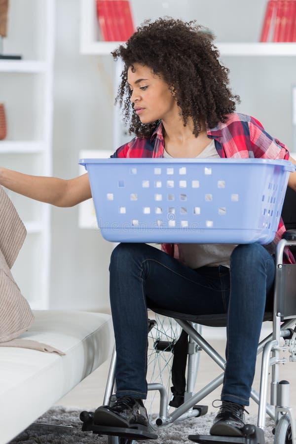 Με ειδικές ανάγκες όμορφη γυναίκα που κάνει το πλυντήριο στοκ φωτογραφία