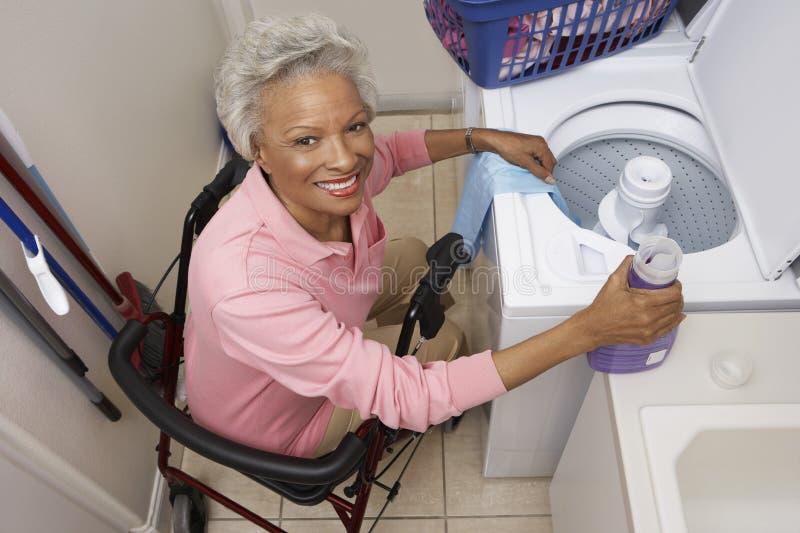 Με ειδικές ανάγκες ανώτερη γυναίκα που κάνει το πλυντήριο στο σπίτι στοκ εικόνες