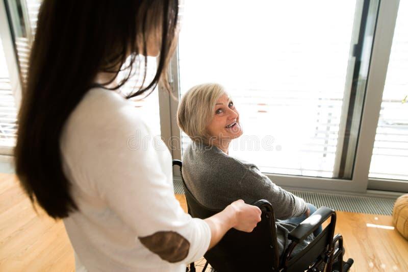 Με ειδικές ανάγκες ανώτερη γυναίκα στην αναπηρική καρέκλα με το νέο daugher της στοκ εικόνες