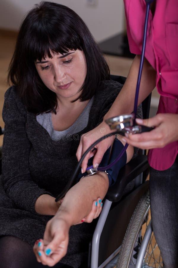 Με ειδικές ανάγκες γυναίκα κατά τη διάρκεια της μέτρησης πίεσης στοκ φωτογραφία