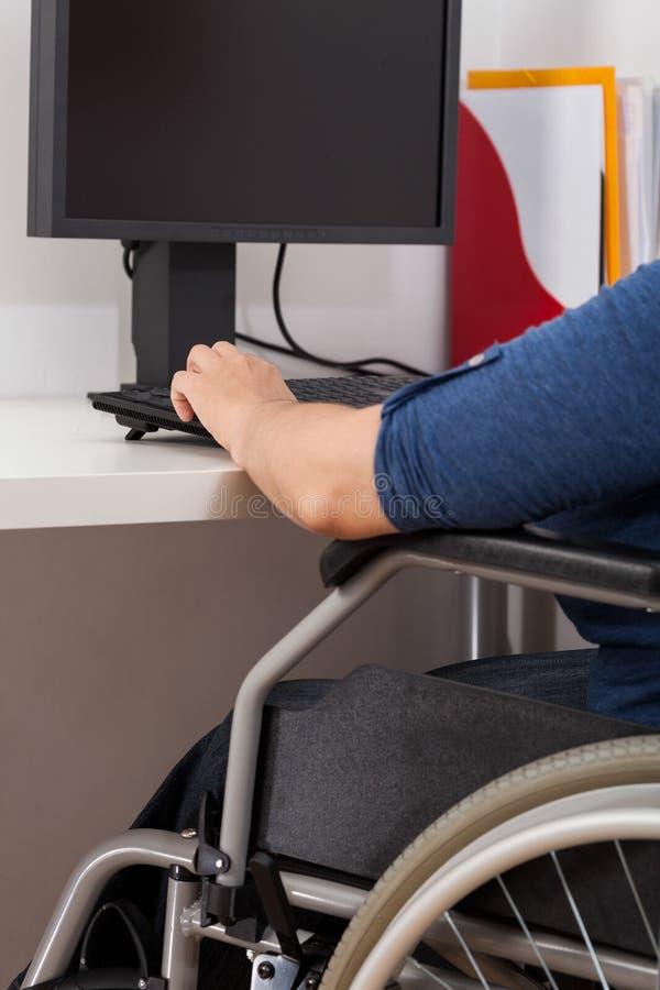 Με ειδικές ανάγκες γυναίκα που εργάζεται δίπλα στον υπολογιστή στοκ εικόνα
