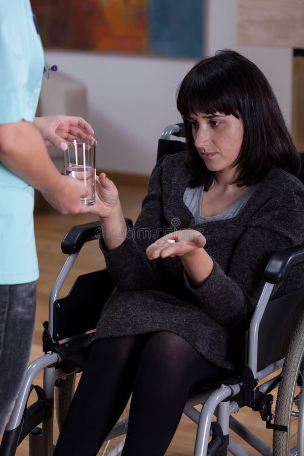 Με ειδικές ανάγκες γυναίκα που παίρνει τα φάρμακα στοκ εικόνα με δικαίωμα ελεύθερης χρήσης