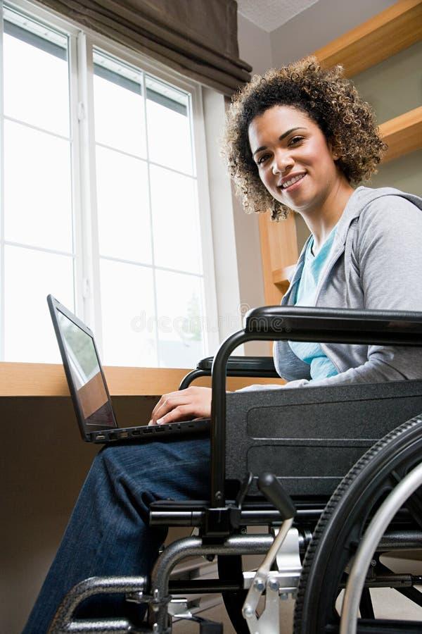 Με ειδικές ανάγκες γυναίκα που χρησιμοποιεί έναν φορητό προσωπικό υπολογιστή στοκ εικόνες