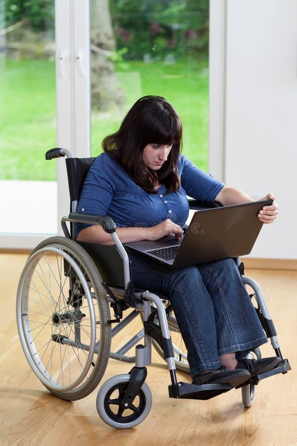 Με ειδικές ανάγκες γυναίκα που χρησιμοποιεί το lap-top στοκ εικόνες με δικαίωμα ελεύθερης χρήσης