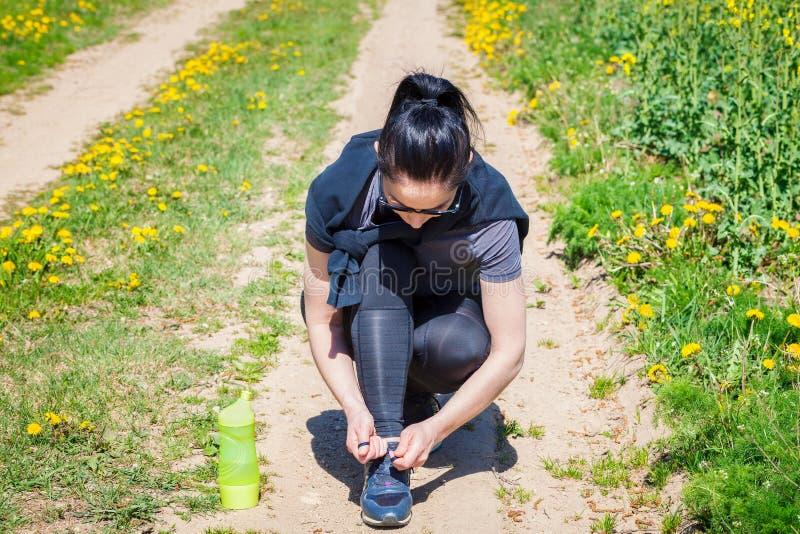 Με κορδόνια πάνινα παπούτσια γυναικών μετά από να τρέξει στον αγροτικό δρόμο στοκ φωτογραφία