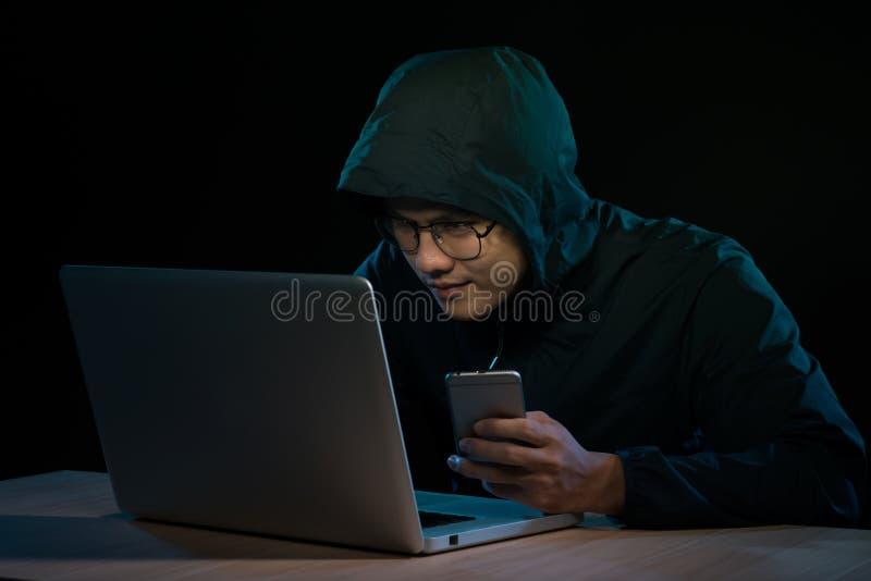 Με κουκούλα χάκερ εγκλήματος cyber που χρησιμοποιεί το κινητό τηλέφωνο Διαδίκτυο που χαράσσει μέσα στοκ φωτογραφία με δικαίωμα ελεύθερης χρήσης