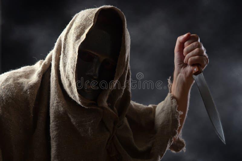 Με κουκούλα άτομο με το μαχαίρι στοκ φωτογραφία με δικαίωμα ελεύθερης χρήσης