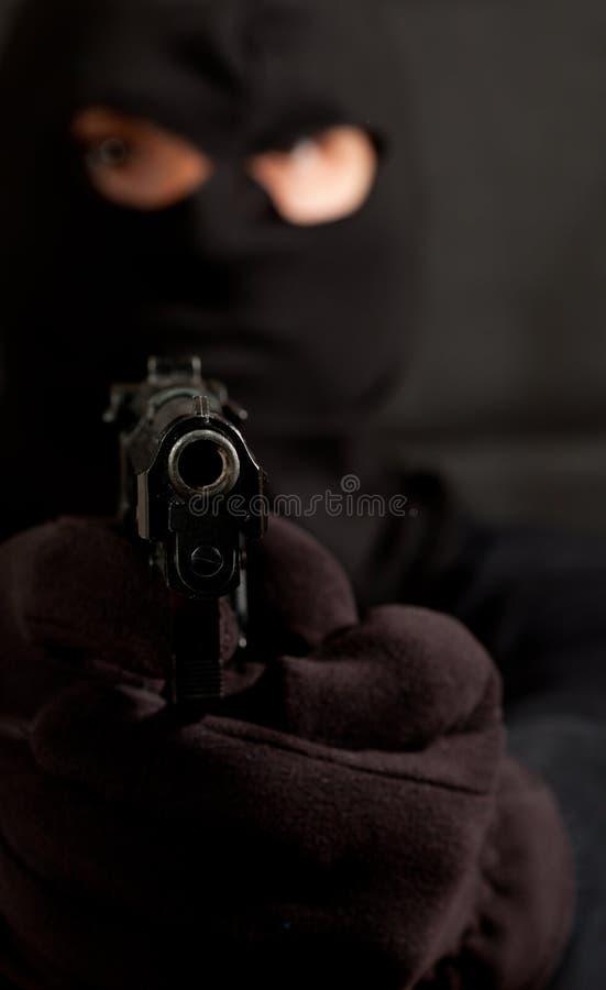 Με κουκούλα ληστής με ένα πυροβόλο όπλο στοκ φωτογραφία με δικαίωμα ελεύθερης χρήσης