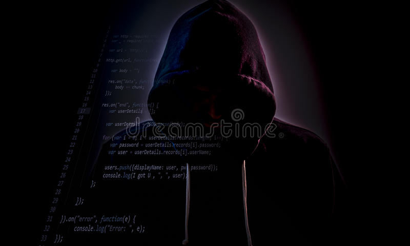 Με κουκούλα χάκερ στο σκοτάδι με τον κώδικα στοκ φωτογραφίες
