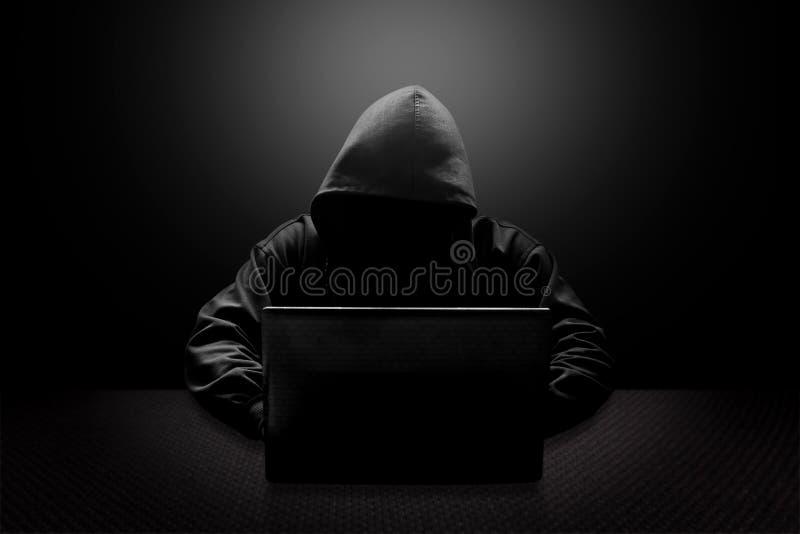 Με κουκούλα stealing πληροφορίες χάκερ υπολογιστών στοκ φωτογραφίες με δικαίωμα ελεύθερης χρήσης