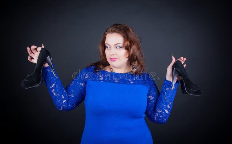 Με μεγάλο στήθος κορίτσι σε ένα μπλε φόρεμα που κρατά τα μαύρα παπούτσια και τις αμφιβολίες στην επιλογή τους στοκ εικόνες
