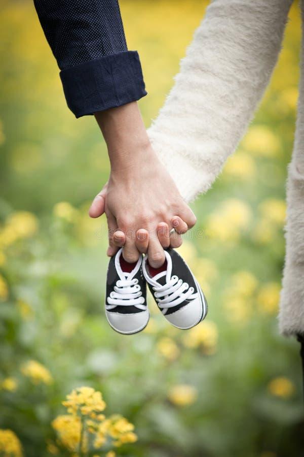 Μελλοντικοί γονείς που κρατούν τα χέρια και ένα ζευγάρι των μικρών παπουτσιών στοκ φωτογραφία