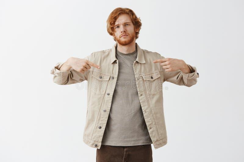 Με χρειάζεστε Δροσερός και βέβαιος ελκυστικός redhead καλλιτεχνικός τύπος στο μπεζ σακάκι πέρα από τη ριγωτή μπλούζα που δείχνει  στοκ φωτογραφία