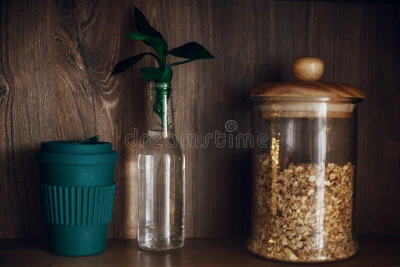Μηά έννοια αποβλήτων, βιώσιμος τρόπος ζωής Βάζο γυαλιού με το granola, το επαναχρησιμοποιήσιμα φλυτζάνι καφέ και τα φύλλα μπαμπού στοκ εικόνες