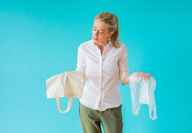 Μηά έννοια αποβλήτων Γυναίκα που επιλέγει να χρησιμοποιήσει την τσάντα πολυ-χρήσης αντί πλαστικής στοκ εικόνες
