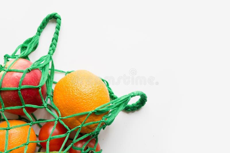 Μηά απόβλητα Πράσινη υφαντική τσάντα αγορών με το φρέσκα πορτοκάλι και τα λαχανικά Διάστημα για το κείμενο στοκ φωτογραφίες