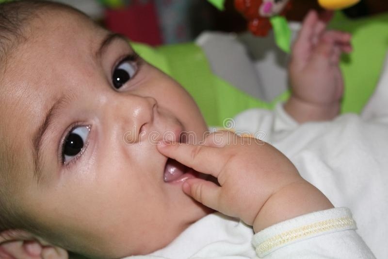 6 μηνών αγοράκι που βάζουν τα δάχτυλά του στο στόμα στοκ εικόνες