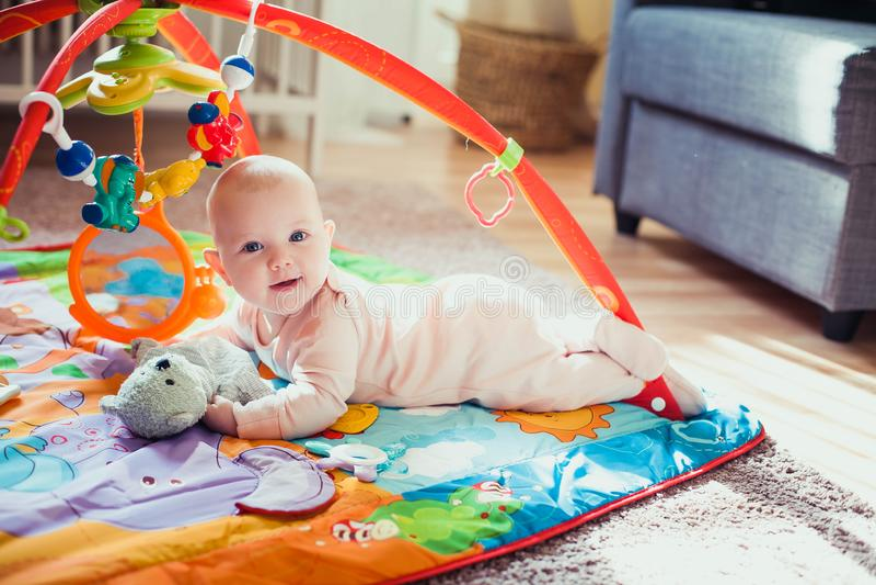 4 μηνών κοριτσάκι ξαπλωμένο σε πολύχρωμο στρώμα παιχνιδιού στο πάτωμα Χαλί δραστηριότητας για παιδιά στοκ φωτογραφία