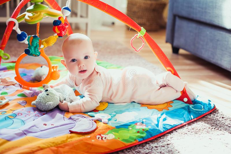 4 μηνών κοριτσάκι ξαπλωμένο σε πολύχρωμο στρώμα παιχνιδιού στο πάτωμα Χαλί δραστηριότητας για παιδιά Πρώιμη ανάπτυξη στο σπίτι στοκ εικόνα με δικαίωμα ελεύθερης χρήσης
