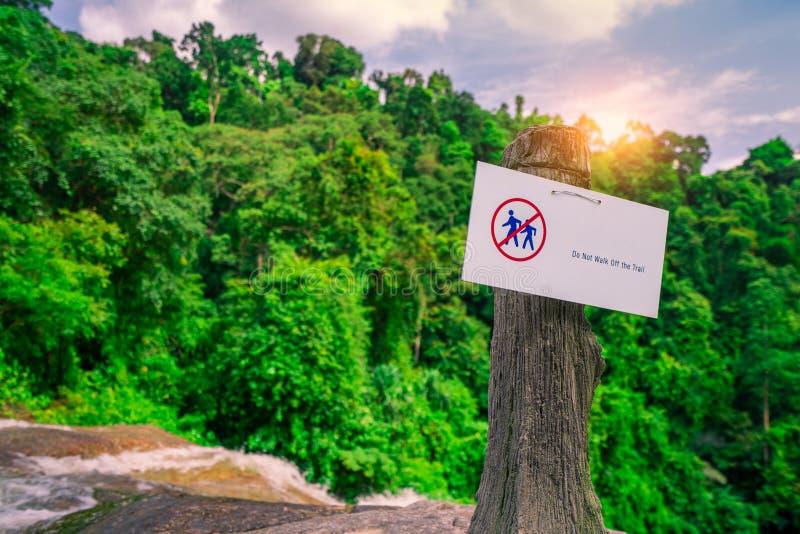 Μην περπατήστε του ίχνους Το προειδοποιητικό σημάδι στο εθνικό πάρκο κρεμά στο συγκεκριμένο πόλο στον καταρράκτη στο πράσινο τροπ στοκ φωτογραφία με δικαίωμα ελεύθερης χρήσης