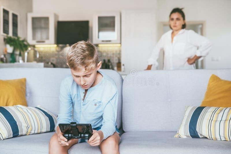 Μητέρα δυστυχισμένη με το γιο εφήβων που πέρασε το ελεύθερο χρόνο του με τη EL στοκ φωτογραφία με δικαίωμα ελεύθερης χρήσης