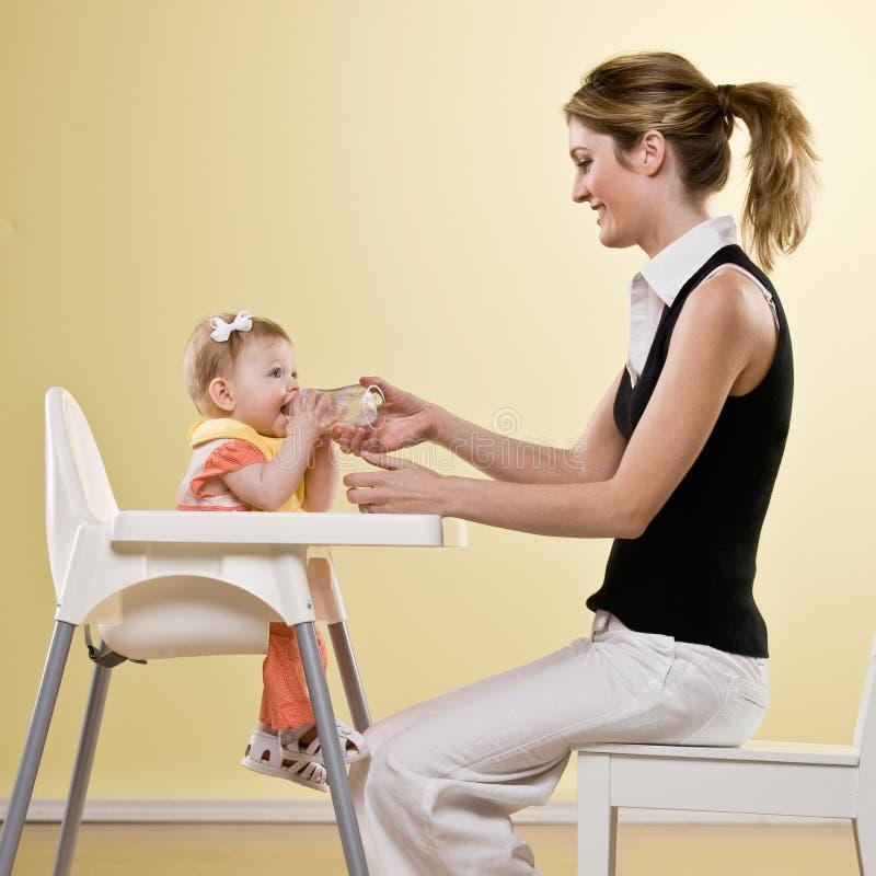 μητέρα εκμετάλλευσης μπουκαλιών μωρών highchair στοκ φωτογραφία