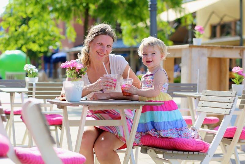 Μητέρα και λίγη κόρη που πίνουν στον καφέ στοκ φωτογραφία