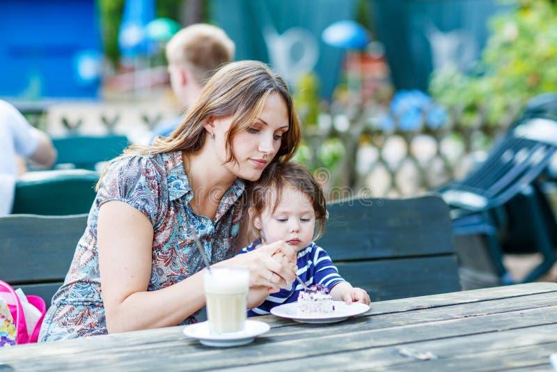 Μητέρα και λίγος λατρευτός καφές κατανάλωσης κοριτσιών παιδιών στο υπαίθριο γ στοκ φωτογραφία