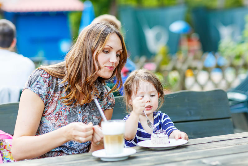 Μητέρα και λίγος λατρευτός καφές κατανάλωσης κοριτσιών παιδιών στο υπαίθριο γ στοκ φωτογραφία με δικαίωμα ελεύθερης χρήσης