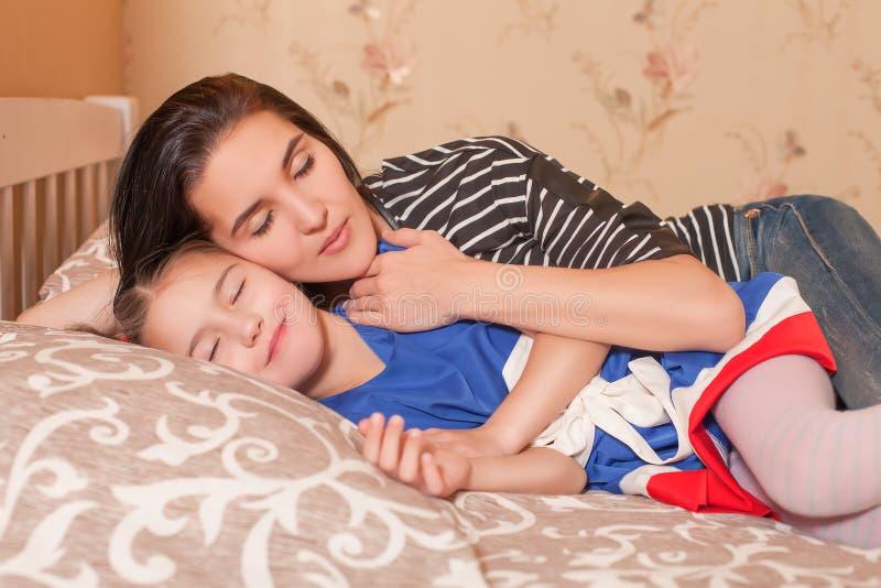Μητέρα και λίγος ύπνος κορών στο κρεβάτι στοκ εικόνες