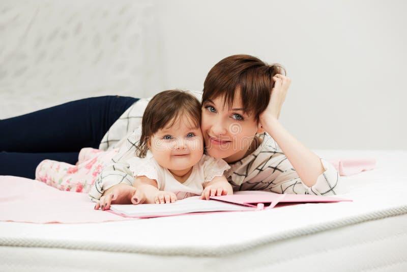 Μητέρα και λίγο κοριτσάκι που διαβάζουν ένα βιβλίο στο κρεβάτι στοκ φωτογραφίες