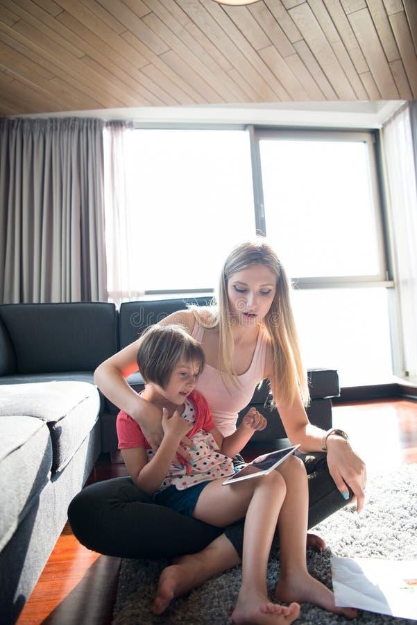 Μητέρα και αυτή λίγη κόρη που χρησιμοποιεί μια ταμπλέτα στο πάτωμα στοκ φωτογραφία με δικαίωμα ελεύθερης χρήσης