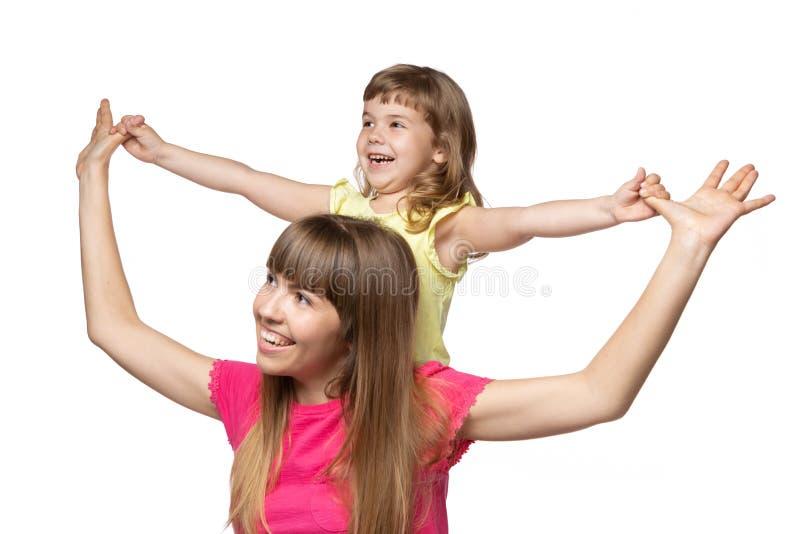 Μητέρα και αυτή χέρια λίγης εκμετάλλευσης κορών, γέλιο, που κοιτάζουν μακριά, συγκινήσεις και χειρονομίες, σε ένα άσπρο υπόβαθρο στοκ φωτογραφία με δικαίωμα ελεύθερης χρήσης