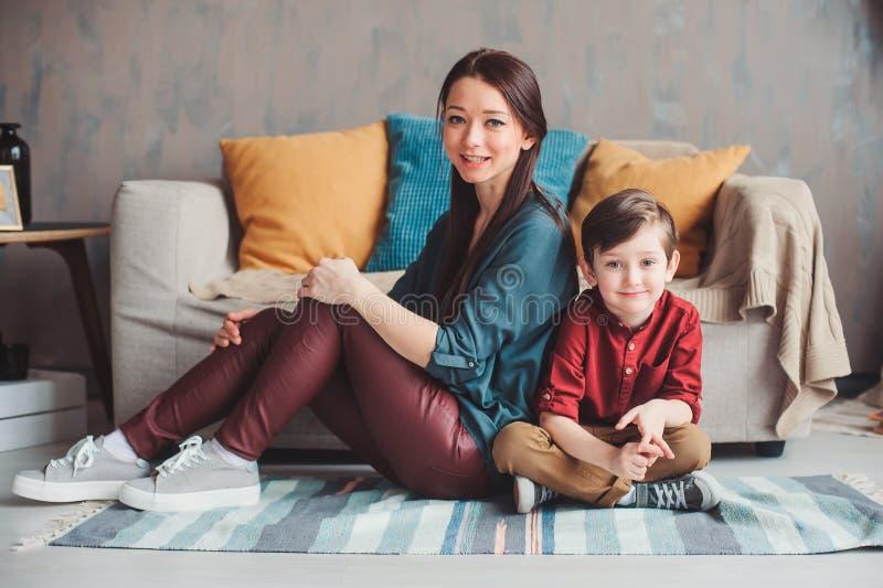 μητέρα και γιος ευτυχείς μαζί στο σπίτι, καθμένος στον άνετο καναπέ στοκ εικόνες