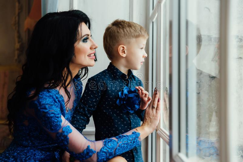 Μητέρα και γιος μαζί κοντά στο μεγάλο παράθυρο στοκ φωτογραφία με δικαίωμα ελεύθερης χρήσης
