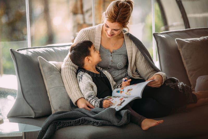 Μητέρα και γιος με το βιβλίο ιστορίας στο σπίτι στοκ φωτογραφία